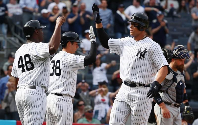 Judge celebrates a two-run homer with Chris Carter and Kyle Higashioki.