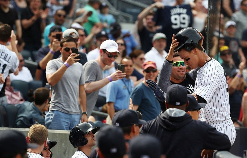 Gary Sanchez removes Judge's helmet after a two-run homer.