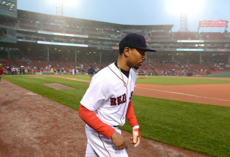Mookie Betts walks across the field during an evening game.
