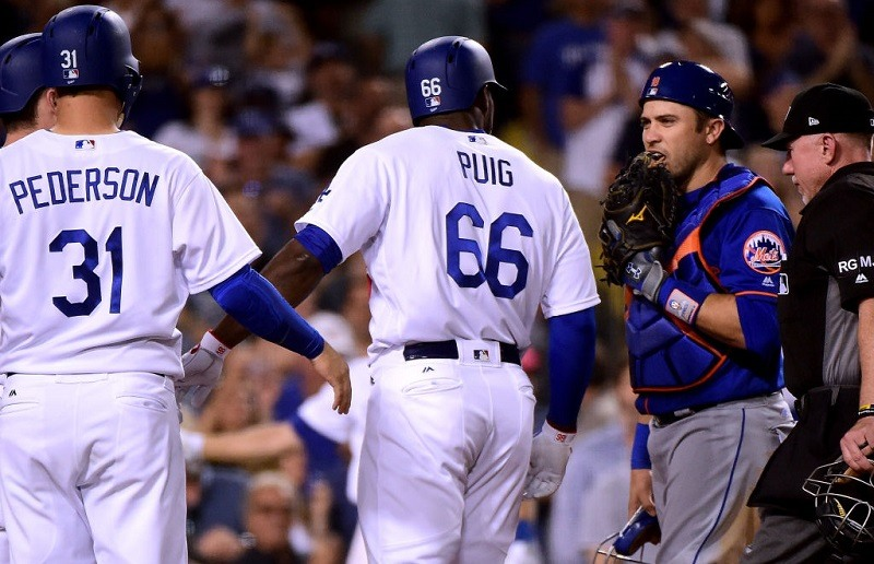 Travid d'Arnaud engages Yasiel Puig at home plate at Dodger Stadium.