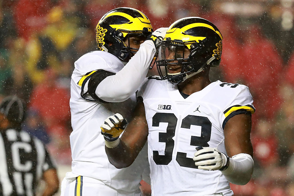 Taco Charlton of the Michigan Wolverines celebrates with his teammate.