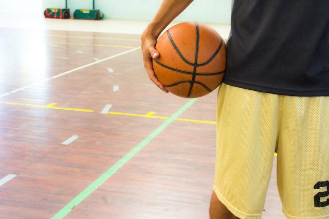 Player with basketball ball in a gym.