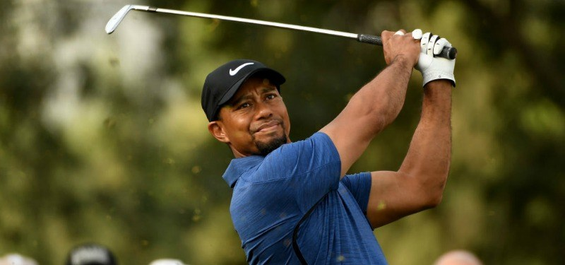 Tiger Woods swings as he is playing golf on the golf course.