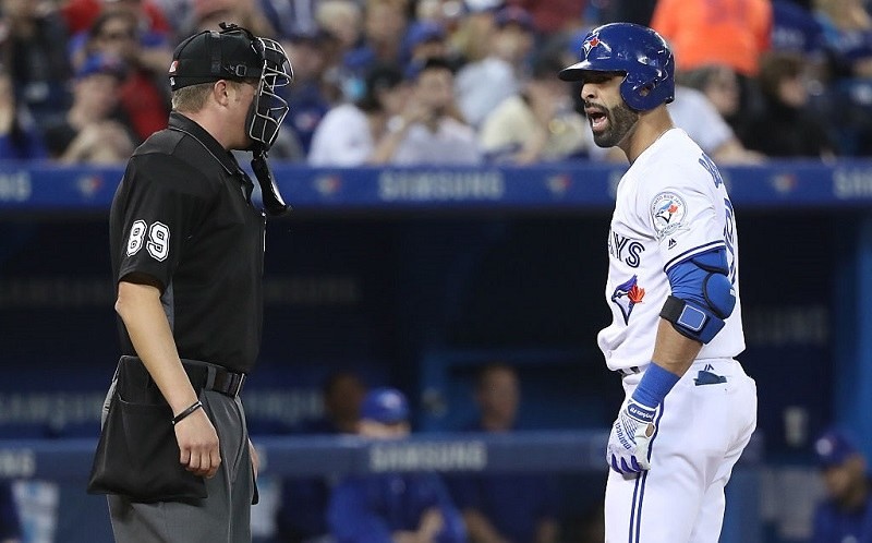 Jose Bautista #19 of the Toronto Blue Jays argues a strike-three call by home plate umpire Cory Blaser #89.