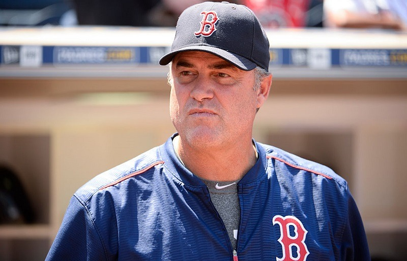 John Farrell #53 of the Boston Red Sox watches from the dugout.