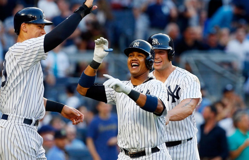 Aaron Judge, Starlin Castro, and Matt Holliday celebrate a home run at Yankee Stadium.