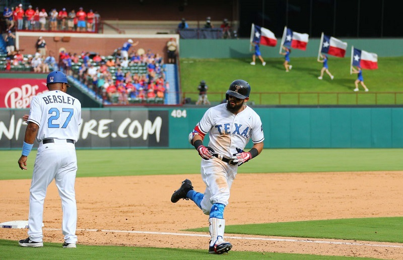 Rougned Odor #12 of the Texas Rangers is congratulated by third base coach Tony Beasley #27 for hitting a solo home run.