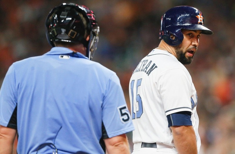 Carlos Beltran #15 of the Houston Astros has words with home plate umpire Greg Gibson after being called out on strikes.