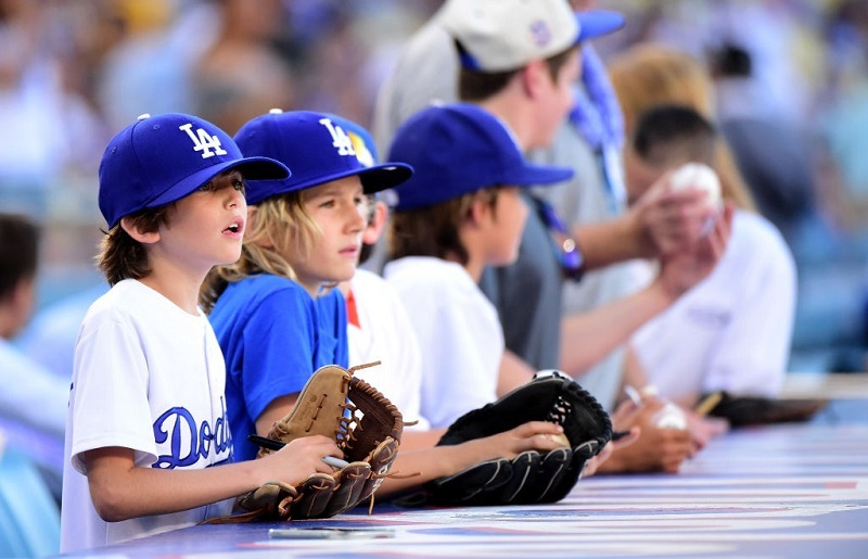Young Dodgers fans look for a ball from players before the game.