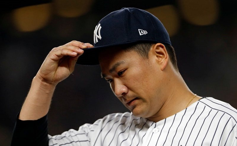 Masahiro Tanaka #19 of the New York Yankees walks back to the dugout.