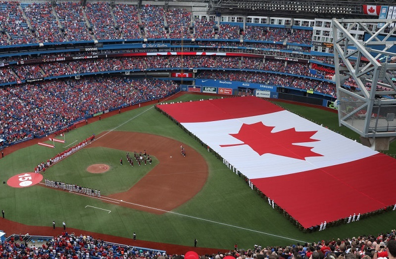 A general view of Rogers Centre as a large Canadian flag is unfurled in the outfield on Canada Day