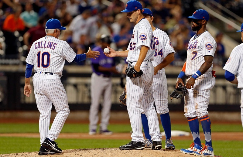 Seth Lugo #67 of the New York Mets hands the ball over to teammate Terry Collins.