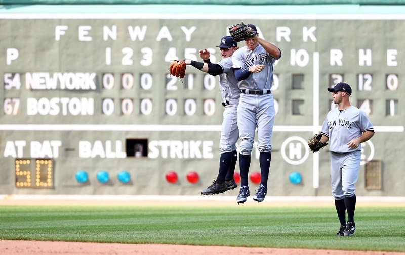 The New York Yankees celebrate an out at Fenway Park.