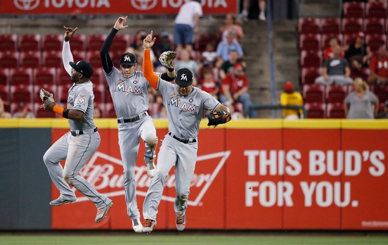 Marcell Ozuna #13, Christian Yelich #21, and Giancarlo Stanton #27 of the Miami Marlins celebrate a win.