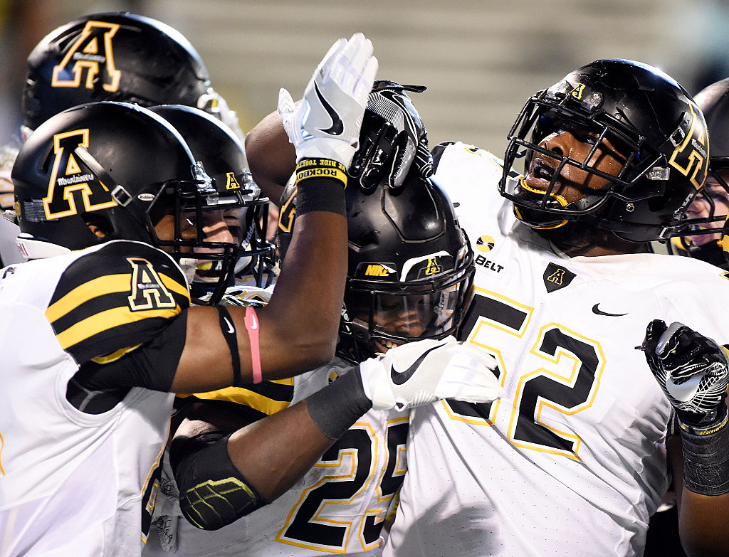 Running back Jalin Moore of the Appalachian State Mountaineers is congratulated by teammates after scoring a touchdown.