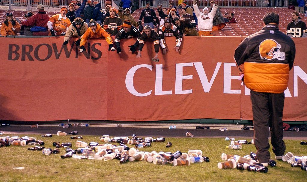 Bottles and debris litter the field at Cleveland Browns Stadium.