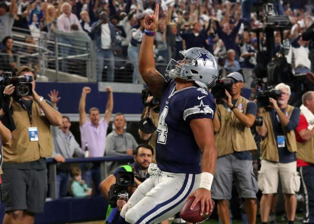 Dak Prescott points to the sky after rushing for a touchdown.