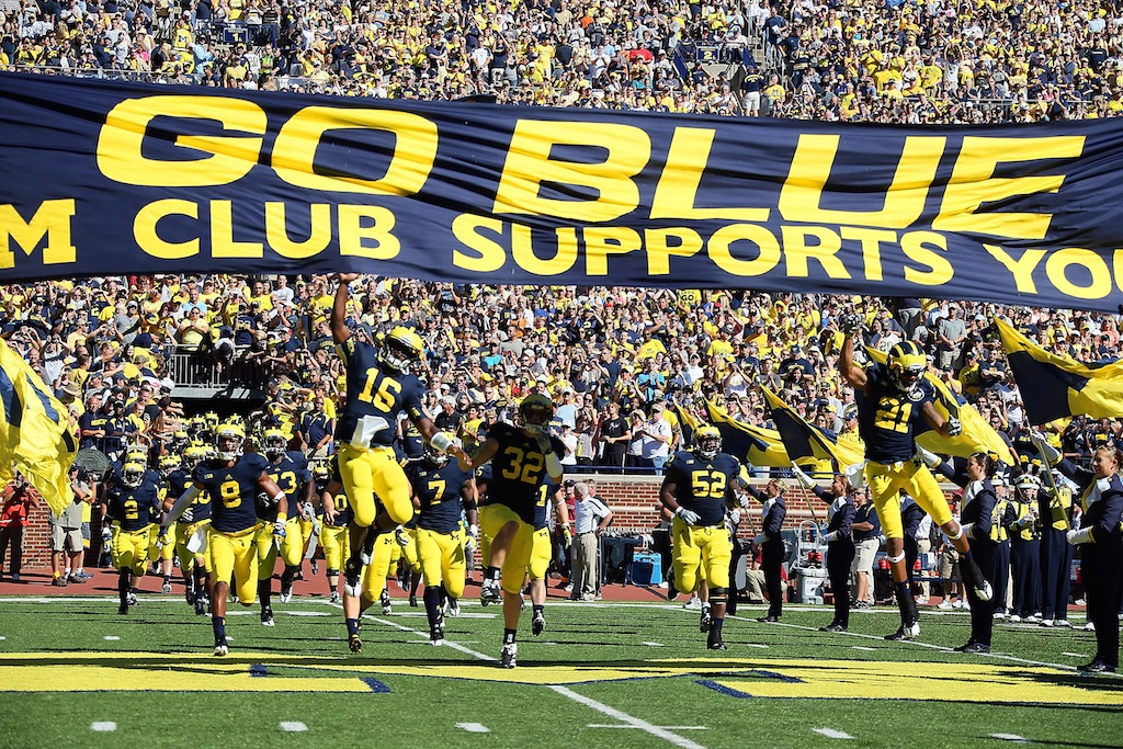 Denard Robinson of the University of Michigan Wolverines leads his team to the field.