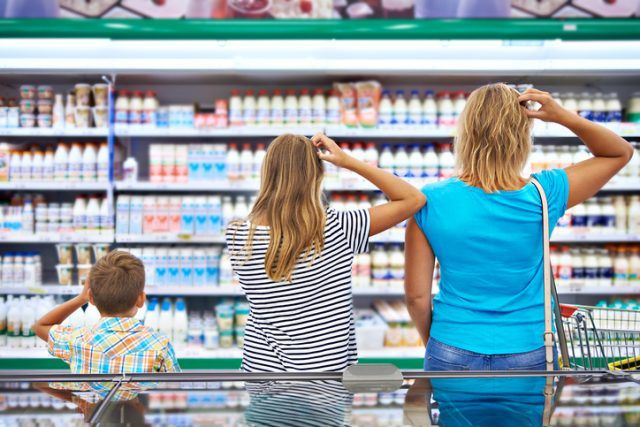 Family chooses dairy products in market.