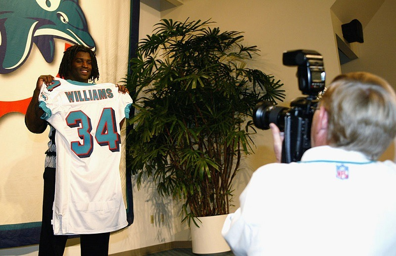 Ricky Williams shows off his Dolphins jersey at a press conference in Miami.
