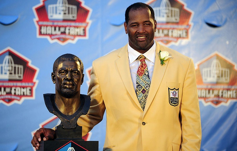 Former Chicago Bears defensive end Richard Dent poses with his bust at the Pro Football Hall of Fame.