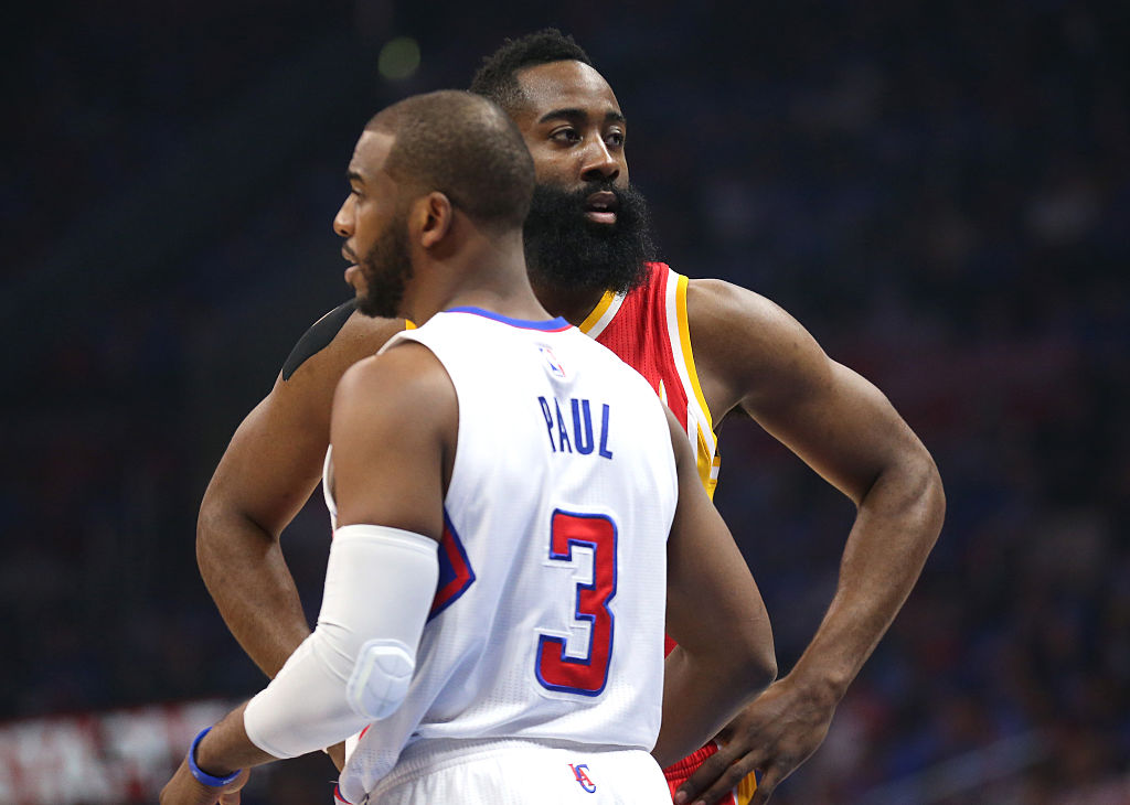 Chris paul and James Harden talk on the court.