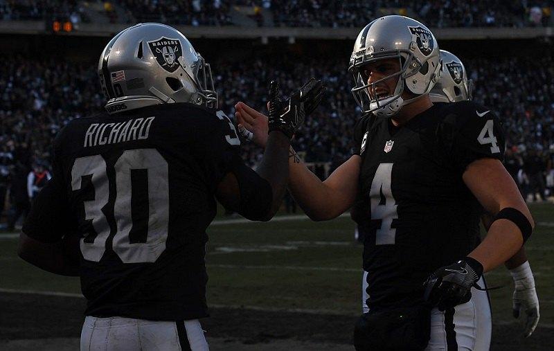 Raiders QB Derek Carr and teammate talk during an NFL game.