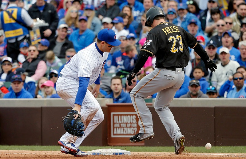 Cubs first baseman Anthony Rizzo makes an error while David Freese crosses the bag.