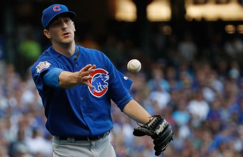 Kyle Hendricks tosses his teammate the ball during a game.