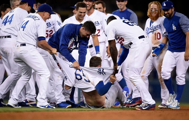 Kyle Farmer #65 of the Los Angeles Dodgers has his shirt ripped apart by teammates.