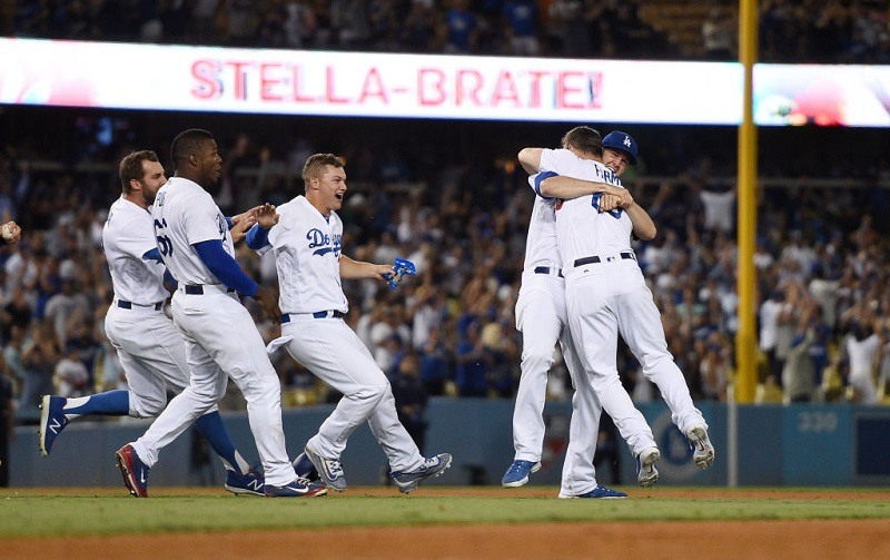 Kyle Farmer #65 of the Los Angeles Dodgers is congratulated by teammates after hitting a game-winning double.