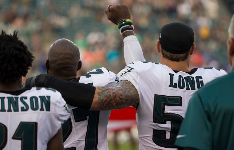 Malcolm Jenkins #27 of the Philadelphia Eagles holds his fist in the air while Chris Long #56 of the Philadelphia Eagles puts his arm around him during the national anthem.