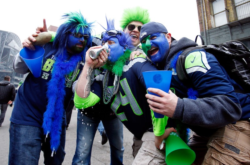 Seattle Seahawks fans drink a beer before a game.
