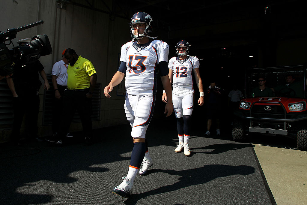 Trevor Siemian and Paxton Lynch of the Denver Broncos walk out to the field prior to the start of a game.