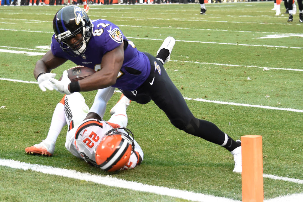 Benjamin Watson of the Baltimore Ravens dives over Jabrill Peppers of the Cleveland Browns to score a touchdown.