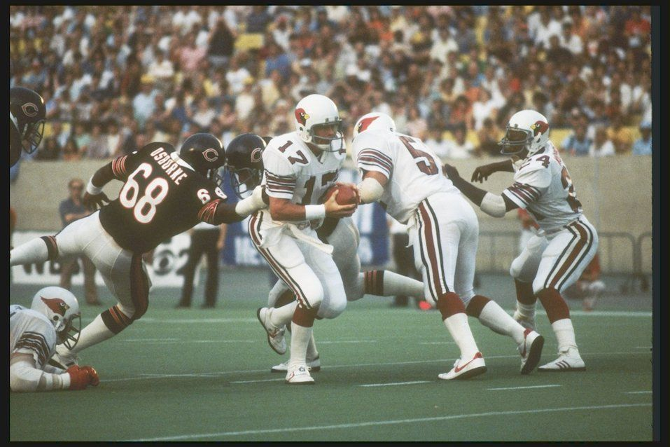 St Louis Cardinals quarterback Jim Hart avoids the grasp of a Chicago Bears defensive lineman during a preseason game