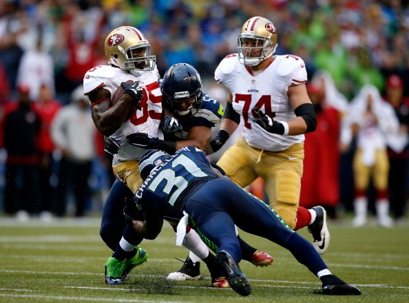 Vernon Davis #85 of the San Francisco 49ers gets tackled by Mike Morgan #57 and Kam Chancellor #31 of the Seattle Seahawks