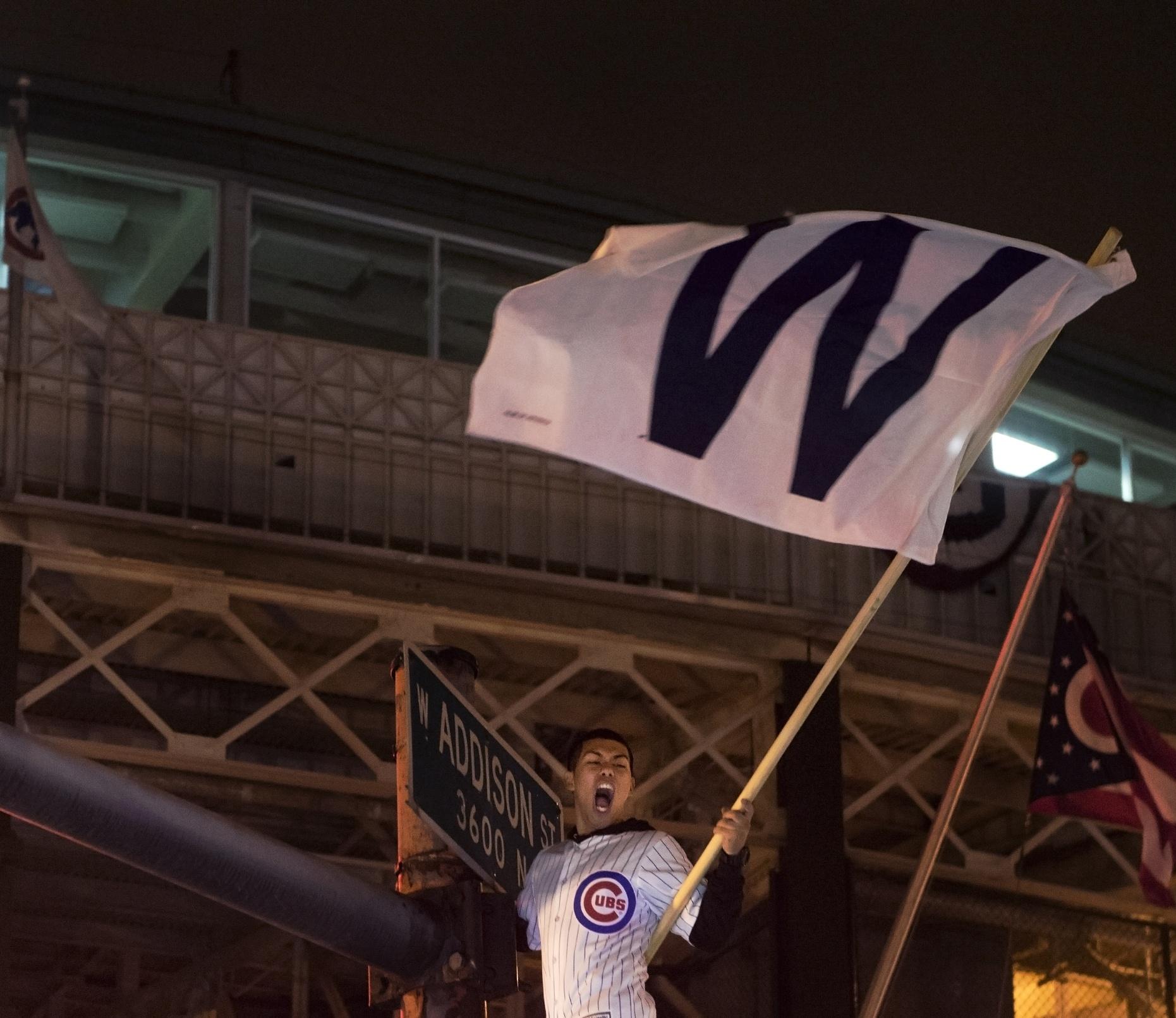 a fan waves a W flag outside wrigley field