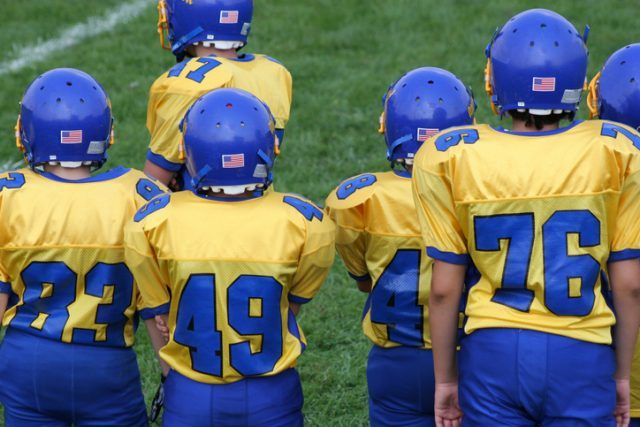 Kids in football uniforms on the sidelines.