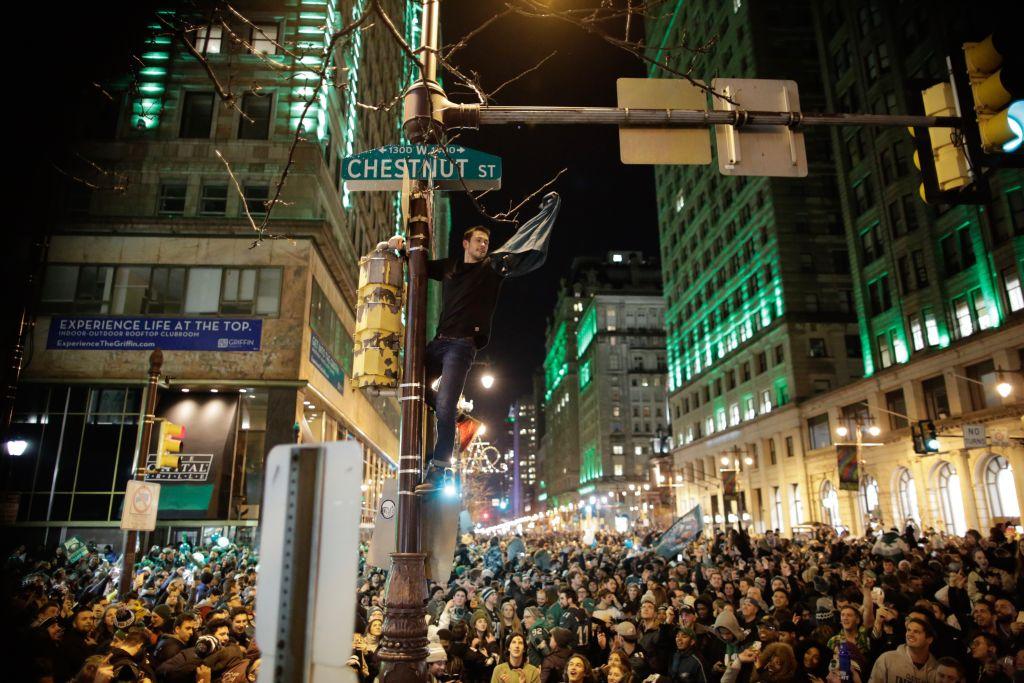 A man climbs a traffic pole as Philadelphia Eagles fans celebrate