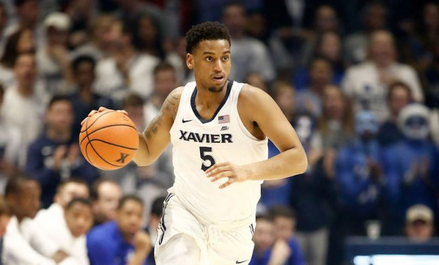 Trevon Bluiett dribbling a basketball on the court.