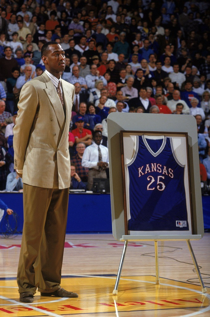 Former University of Kansas Jayhawk Danny Manning stands in center court next to his framed #25 Jayhawk jersey during a Kansas game.