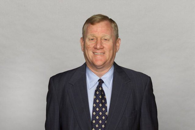 Bill Polian smiling in front of a gray wall.