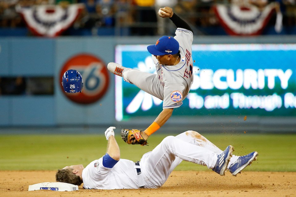 Ruben Tejada #11 of the New York Mets is hit by a slide by Chase Utley #26 of the Los Angeles Dodgers in the seventh inning