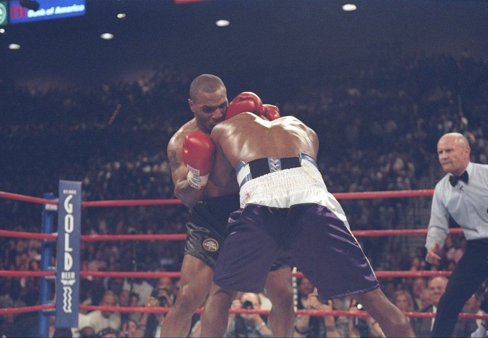 Evander Holyfield and Mike Tyson lock heads during their heavyweight title fight at the MGM Grand Garden
