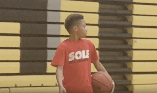 Jordan Lowery holding a basketball inside a gym.