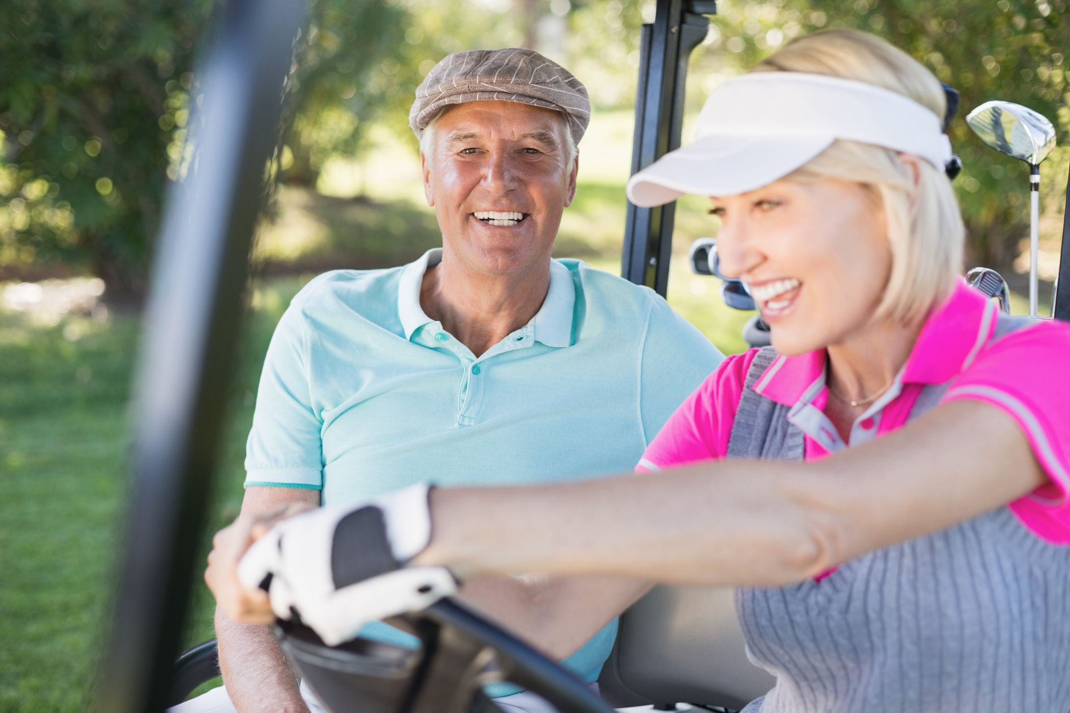 Mature couple enjoying in golf cart
