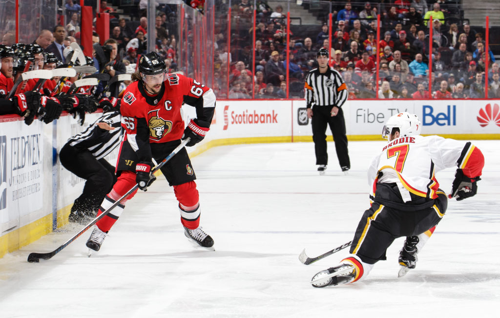 TJ Brodie of the Calgary Flames goes down on a knee to successfully block a pass from Erik Karlsson of the Ottawa Senators.