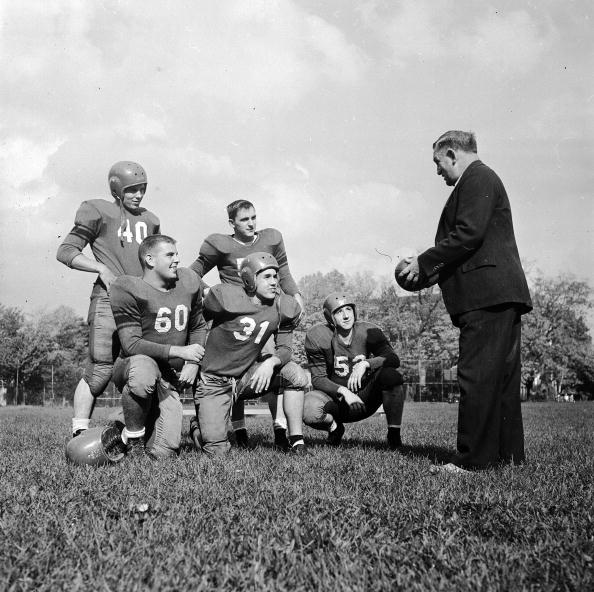 Harold Poor, coach of Pennington School's American Football team, explains a new play to a group of his pupils.