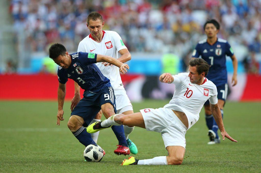 Grzegorz Krychowiak tackles Shinji Okazaki during the World Cup